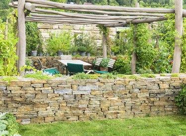 Idyllic garden scene gazebo outdoor furniture stone wall