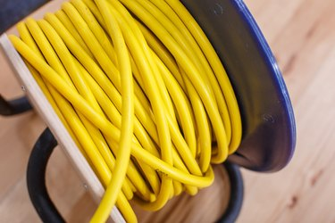 Yellow electric wire extension cord on the reel
