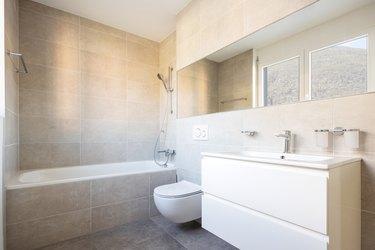 Modern minimal bathroom with large tile bathtub