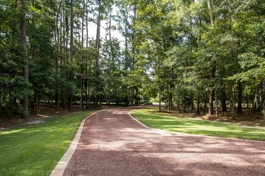 long red gravel driveway to a custom home