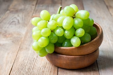 Bunch of green ripe grapes in wooden bowl, copy space