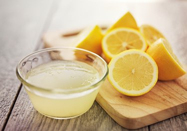 Small glass bowl of lemon juice and several lemon halves arranged on a wooden cutting board