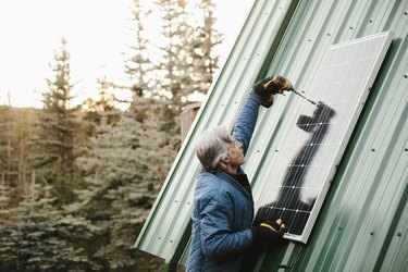 Man installing solar panel on cabin roof.