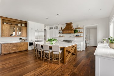 beautiful kitchen in new luxury home with island, pendant lights, and hardwood floors.