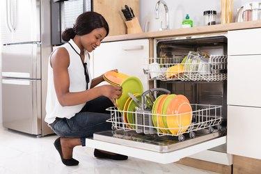 Woman Arranging Plates In Dishwasher