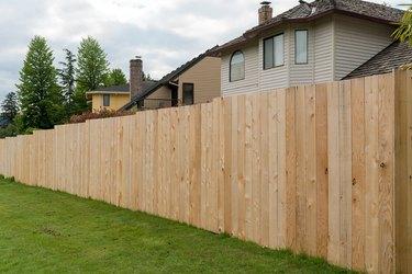 New Cedar wood fence boards along homes in suburban neighborhood