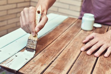 young man painting an old wooden table