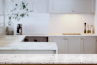 Empty white marble  table top and  kitchen background. for food and product display montage