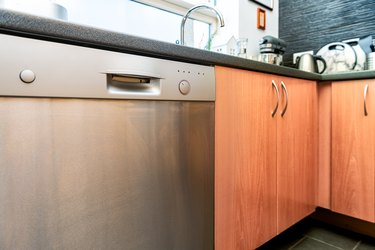 Modern wooden kitchen drawers cabinets and dishwasher with utensils, equipment and nobody