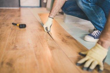 Closeup of master laying laminate flooring