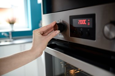 Close up of woman's hand setting temperature control on oven