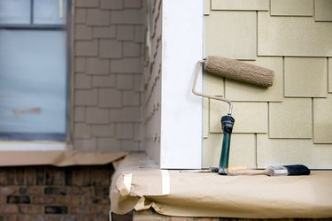 Paint Roller, Brush and Putty Knife rest near New Siding
