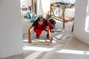 Installing ceramic floor tiles - measuring and cutting the pieces, closeup