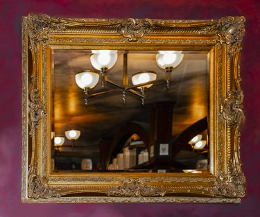 A dark red faux painted marbilized wall with an ornate golden mirror reflecting a warm rustic room with light fixture and shelving
