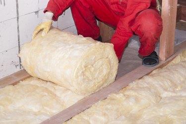 Fiberglass batt insulation being installed.