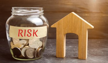 Jar with coins and the word risk and a wooden house. Buying property on credit. The concept of financial risk. Loss of housing for failure to pay. Property insurance. Mortgage and tax. Real estate