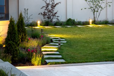 backyard of the mansion with a flowerbed and a lawn of green grass with a marble walkway of square tiles in the evening with a garden lighting with decorative ground lamps illuminating a warm light.