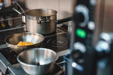 Sauces and soups simmering in restaurant kitchen - Stock photo