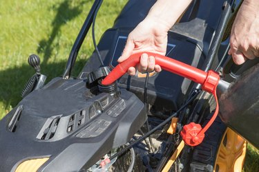 Pouring gasoline into lawn mower