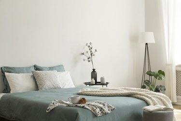 Bedroom interior with sage green and white sheets and cushions and a blanket. Black metal table with vases beside the bed. A lamp standing in the corner. Real photo.