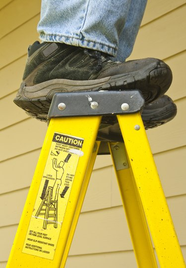 User standing on top of a ladder.