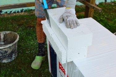 Worker sawing white foam sheet