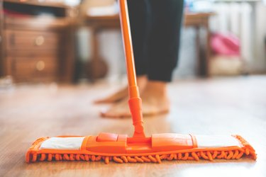 single man holding a mop and cleaning the laminate floor at home