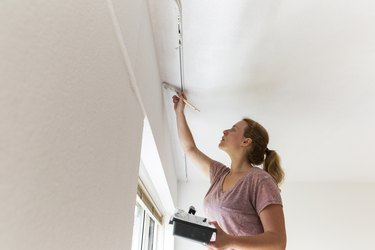 Girl painting living room ceiling.