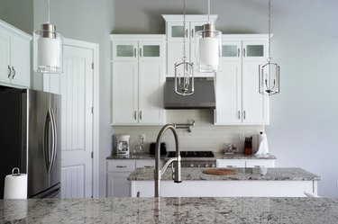 Interior design and kitchen architecture decorated with white wooden furniture, marbled materials and built in appliances