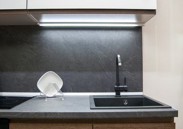 dark gray laminate worktop with black faux stone sink with faucet in a modern kitchen