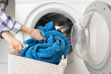 persons hand put dirty clothes in the washing machine b