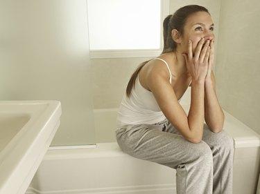 Woman sitting on the edge on bath, resting
