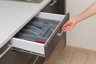 Profile side view photo of part clean white cook table, woman hand open new brown kitchen drawer by modern door handle, with different cutlery spoon, pizza knife, fork and stuff