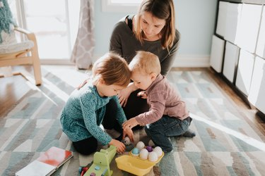 Female toddler playing with mother and baby brother in living room