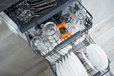 Dishwasher, open and loaded with dishes in the kitchen, after washing. Flat lay.