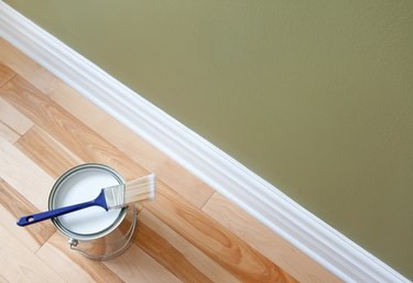 Paintbrush and a can of white paint on wooden floor
