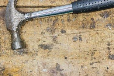 Worn hammer on scratched workbench surface