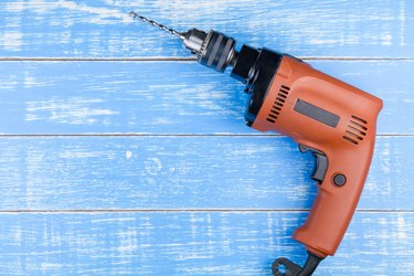 Electric drill with a drill on blue wooden table background