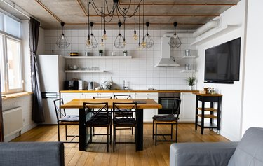 Modern scandinavian an eat-in kitchen interior design with big wooden table and chairs against light wood floor, bright white walls and furnitures with TV, appliances and hanging light bulbs