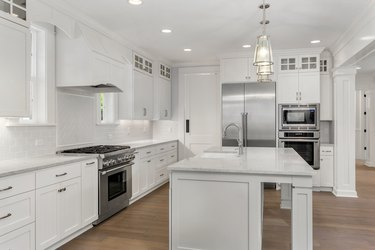 beautiful white kitchen in new luxury home with island, pendant lights, and hardwood floors. Features stainless steel appliances and farmhouse style sink