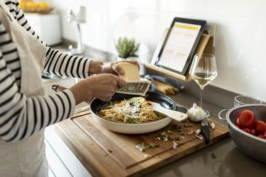 Close-up of woman with tablet cooking pasta dish in kitchen at home