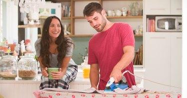 Woman Watching Man Ironing Shirt In Kitchen