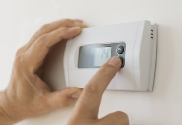 USA, New Jersey, Jersey City, Hand changing settings on air conditioning thermostat