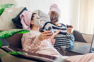 Mother's day. Mother and her adult daughter applied facial masks at home. Women talking while having wine