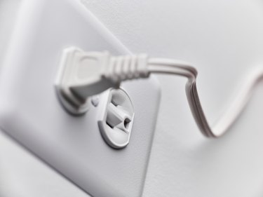Close up of white plug in outlet