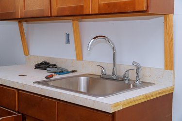 Repairing sink pipe in the kitchen plumber fitting pipes