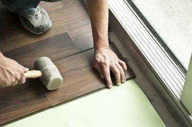 Two male hands holding mallet installing hardwood floor.
