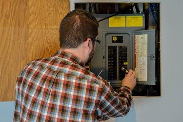 Handyman inspecting an electric box