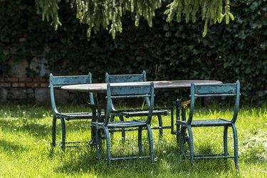 Old iron furniture in garden at springtime