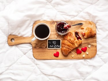 Breakfast tray with a croissant, strawberry jam and a cup of coffee on a white bedspread